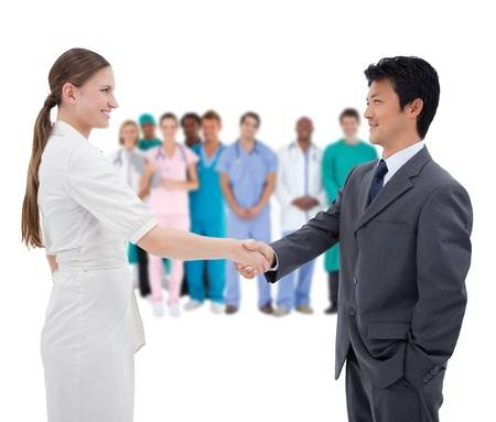 26726994-business-people-shaking-hands-with-medical-staff-in-background-on-white-background